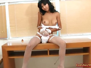 Young Thai shemale Narnia wears a sexy set of white lingerie with matching fishnet stockings